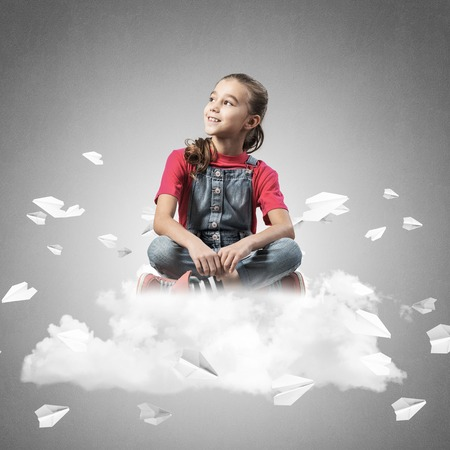 Cute kid girl sitting on cloud and paper planes flying around Stockfoto