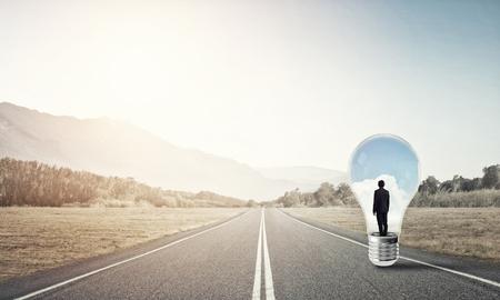Young businessman trapped inside of light bulb on asphalt road