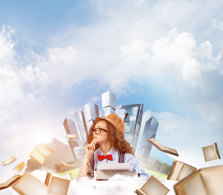 Young and beautiful woman writer in hat and eyeglasses using typing machine while sitting at the table among flying books with floating city island and cloudy skyscape on background.
