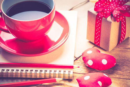 Blank notepad coffee cup and love hearts on wooden table Фото со стока