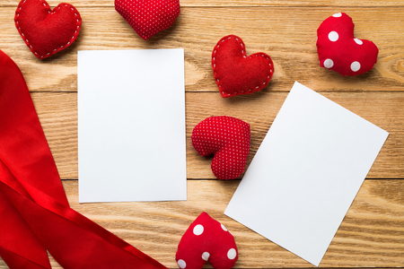 Love hearts and sheet of blank paper on wooden table