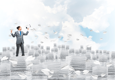 Businessman in suit standing on pile of documents among flying paper planes with speaker in hand with cloudly skyscape on background. Mixed media.