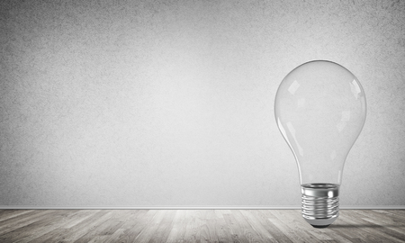 Transparent glass lightbulb in empty room with grey wall on background. 3D rendering.