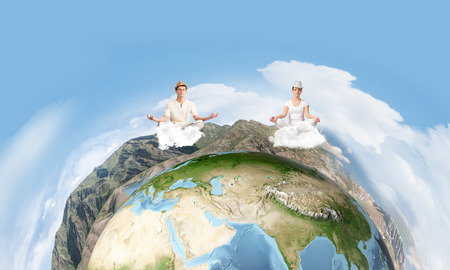 Young couple keeping eyes closed and looking concentrated while meditating on clouds in the air with panoramic view of Earth globe on background. Elements of this image are furnished by NASA