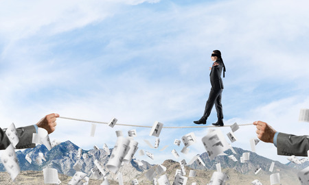 Businessman walking blindfolded on rope among flying documents and above high mountains as symbol of hidden threats and support. Nature view on background. Reklamní fotografie