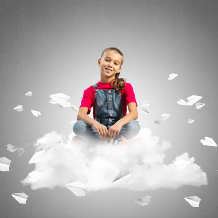Cute kid girl sitting on cloud and paper planes flying around Stock Photo