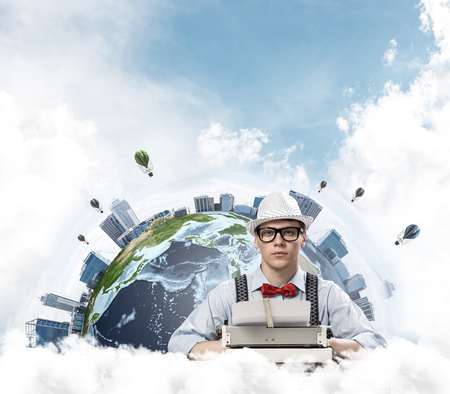 Young man writer in hat and eyeglasses using typing machine while sitting at the table with Earth globe and cloudy skyscape on background.
