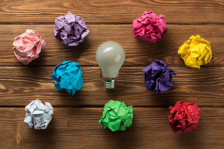 Set of multiple colorful crampled paper ball and lightbulb among them, placed on wooden table as means of searching of new ideas.