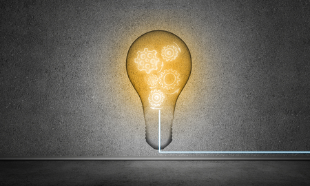 Glass lightbulb with multiple sketched gears inside placed in empty room with grey wall on background. 3D rendering. Stock Photo