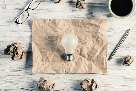 Top view of modern creative workplace with lightbulb on creased piece of sheet, crumpled paper balls and cup of coffee placed on wooden table. Concept of finding of outstanding idea.