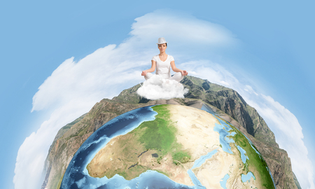 Young woman keeping eyes closed and looking concentrated while meditating on clouds in the air with panoramic view of Earth globe on background.