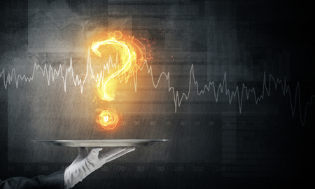 Cropped image of waitresss hand in white glove presenting flaming question mark on metal tray with dark wall on background.