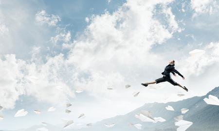 Attractive business woman in suit jumping in the air among flying paper planes as symbol of active life position. Skyscape and nature view on background. 3D rendering.