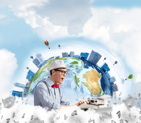 Emotional young man writer in hat and eyeglasses feeling surprised while using typing machine at the table with flying letters and Earth globe among cloudy skyscape on background.