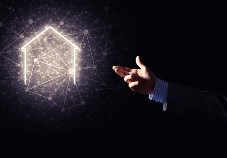 Businessman hand presenting glowing home icon or symbol Reklamní fotografie