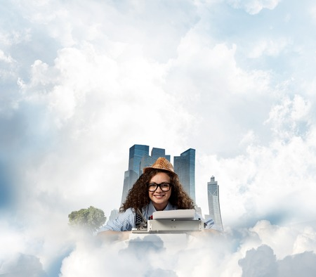 Young and beautiful woman writer in hat and eyeglasses using typing machine while sitting at the table with floating city island and cloudy skyscape on background.