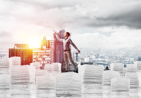 Side view of man in casual wear keeping hand with book up while standing on pile of documents with cityscape and sunlight on background. Mixed media. Stock Photo