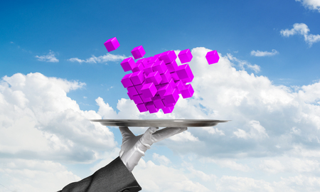 Cropped image of waiters hand in white glove presenting multiple cubes on metal tray with cloudy skyscape on background. 3D rendering. Stock Photo