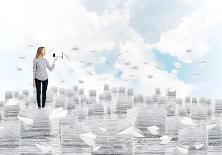 Woman in casual clothing standing on pile of documents among flying paper planes with speaker in hand with cloudly skyscape on background. Mixed media. Stock Photo