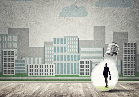 Businesswoman inside light bulb against city drawn concept Stock Photo
