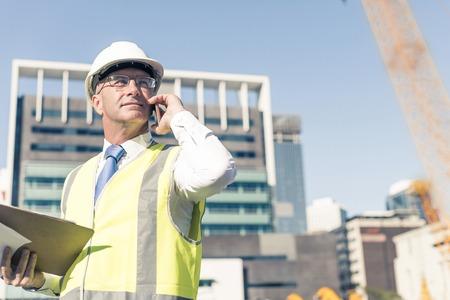 Senior engineer man in suit and helmet talking mobile phone Stock Photo