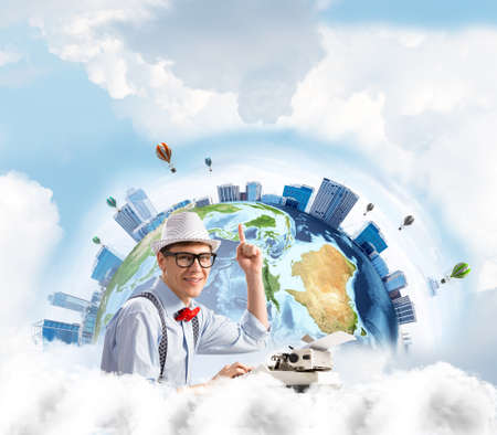 Handsome man writer in hat and eyeglasses pointing up while using typing machine at the table with Earth globe and cloudy skyscape on background. Elements of this image furnished by NASA Stock Photo
