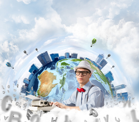 Young man writer in hat and eyeglasses using typing machine while sitting at the table with flying letters and Earth globe among cloudy skyscape on background. Elements of this image furnished by NASA