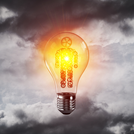 Glass lightbulb with human from gears inside with grey cloudly skyscape on background. 3D rendering.