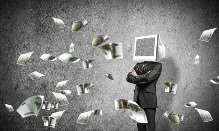 Businessman in suit with monitor instead of head keeping arms crossed while standing among flying euros and with gray dark wall on background. Stock Photo