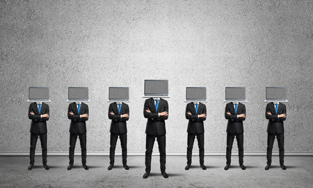 Businessmen in suits with laptops instead of their heads keeping arms crossed while standing in a row in empty room with gray wall on background.
