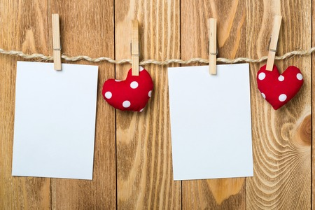 Blank sheet of paper hand made heart pinned to rope on wooden background Фото со стока