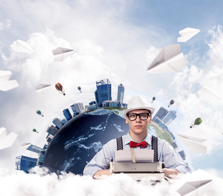 Young man writer in hat and eyeglasses using typing machine while sitting at the table with flying paper planes and Earth globe among cloudy skyscape on background.