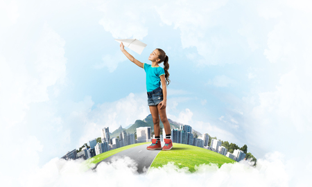 Cute kid girl on city floating island throwing paper plane Imagens