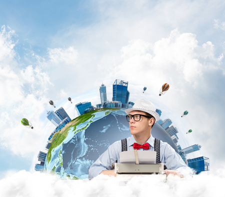 Portrait of man writer looking away and using typing machine while sitting at the table with panoramic Earth and cloudy skyscape on background. Stock Photo