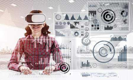 Portrait of beautiful and young woman in checkered shirt using virtual reality goggles and interracting with digital media interface while sitting inside bright office building. Stock Photo