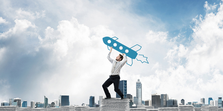 Ambitious and young businessman in suit throwing big drawn rocket from hand while standing on paper column with cityscape view on background