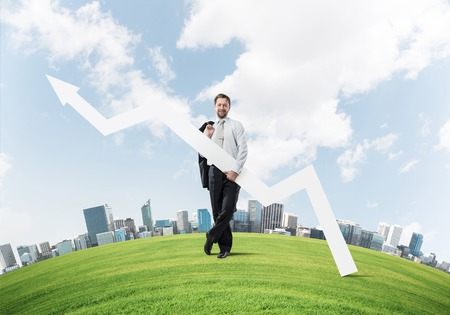 Horizontal shot of confident businessman holding jacket behind his back in one hand and white big arrow in another hand while standing at green meadow and cityscape view on background.