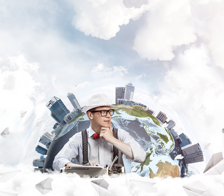 Thoughtful man writer in hat and eyeglasses looking away and touching chin while using typing machine with flying paper planes and Earth globe among cloudy skyscape on background.