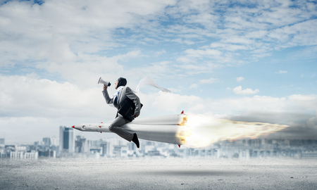 Conceptual image of young businessman in suit flying on rocket above asphalt road with cityscape and blue sky on background.
