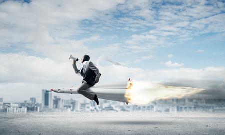 Image conceptuelle du jeune homme d'affaires en costume volant sur une fusée au-dessus de la route goudronnée avec paysage urbain et ciel bleu sur fond.