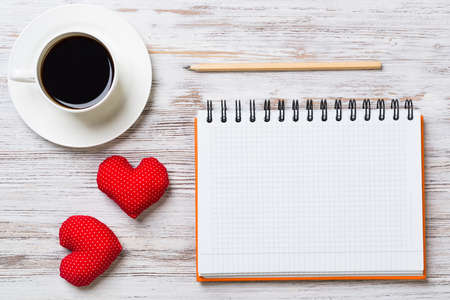 Coffee cup notepad pencil and two red hearts on wooden surface Stock Photo