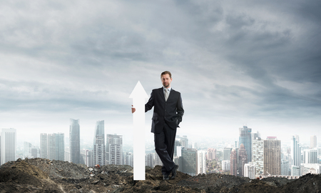 Conceptual image of young businessman keeping big white arrow in hands while standing against cityscape view and cloudy sky on background. Foto de archivo