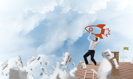 Horizontal shot of successful and young businessman standing on the top of brick roof among flying papers and throwing huge red rocket in the air with cloudy skyscape view on background.