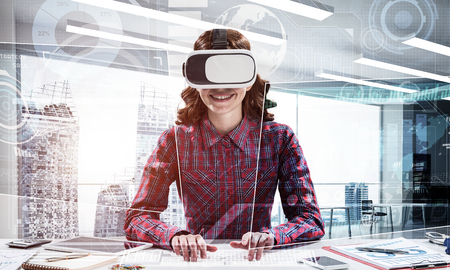 Portrait of beautiful and young woman in red checkered shirt using VR goggles and interracting with digital media interface while sitting inside bright office building. Virtual reality device Stock Photo - 104810498