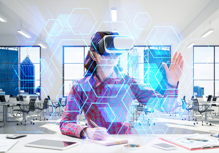Horizontal shot of young woman in checkered shirt using virtual reality headset with media interface while sitting inside bright building. VR technologies for educational process Stock Photo