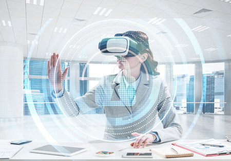 Beautiful and young business woman in suit using virtual reality headset with digital media structure while standing inside office. Up to date security technologies