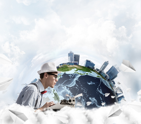 Side view of hard-working man writer using typing machine while sitting at the table with flying paper planes and Earth globe among cloudy skyscape on background. Stock Photo