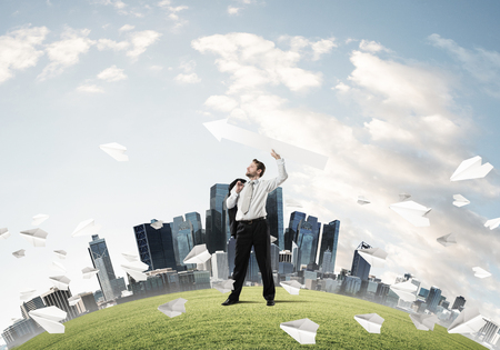 Young and confident businessman in suit starting launching huge white arrow to the air while standing among flying paper planes on green lawn and cityscape view on background.