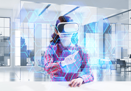Beautiful and young woman in red checkered shirt using VR goggles and interracting with digital media interface while sitting inside bright office building. Virtual reality device Stock Photo - 104938519