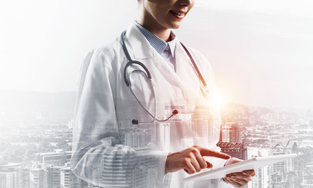 Close up image of medical employee in white suit using tablet and standing outdoors with city view on background. Medical industry concept. Double exposure